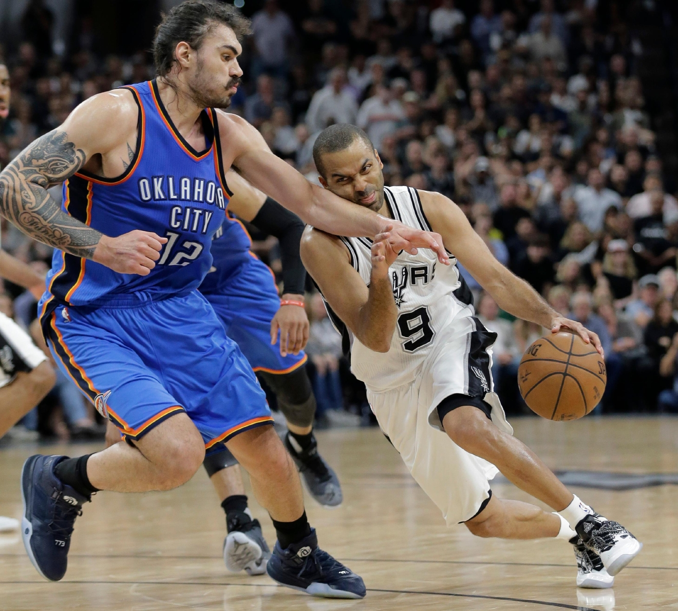 San Antonio Spurs guard Tony Parker (9) is fouled as he drives around Oklahoma City Thunder center Steven Adams (12) during the second half in Game 5 of a second-round NBA basketball playoff series, Tuesday, May 10, 2016, in San Antonio. Oklahoma City won 95-91. (AP Photo/Eric Gay)