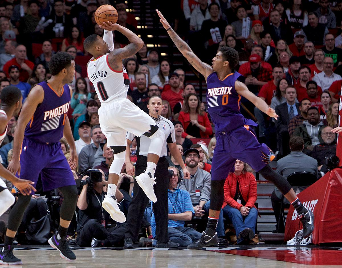 Portland Trail Blazers guard Damian Lillard, left, shoots over Phoenix Suns forward Marquese Chriss during the second half of an NBA basketball game in Portland, Ore., Tuesday, Nov. 8, 2016. The Trail Blazers won 124-121. (AP Photo/Craig Mitchelldyer)
