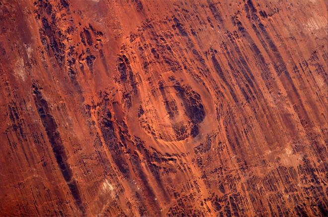 Aorounga Impact Crater in Chad.  345 million years old impact crater marked with linear ridges from wind erosion.  (Photo & Caption courtesy Koichi Wakata (@Astro_Wakata) and NASA)