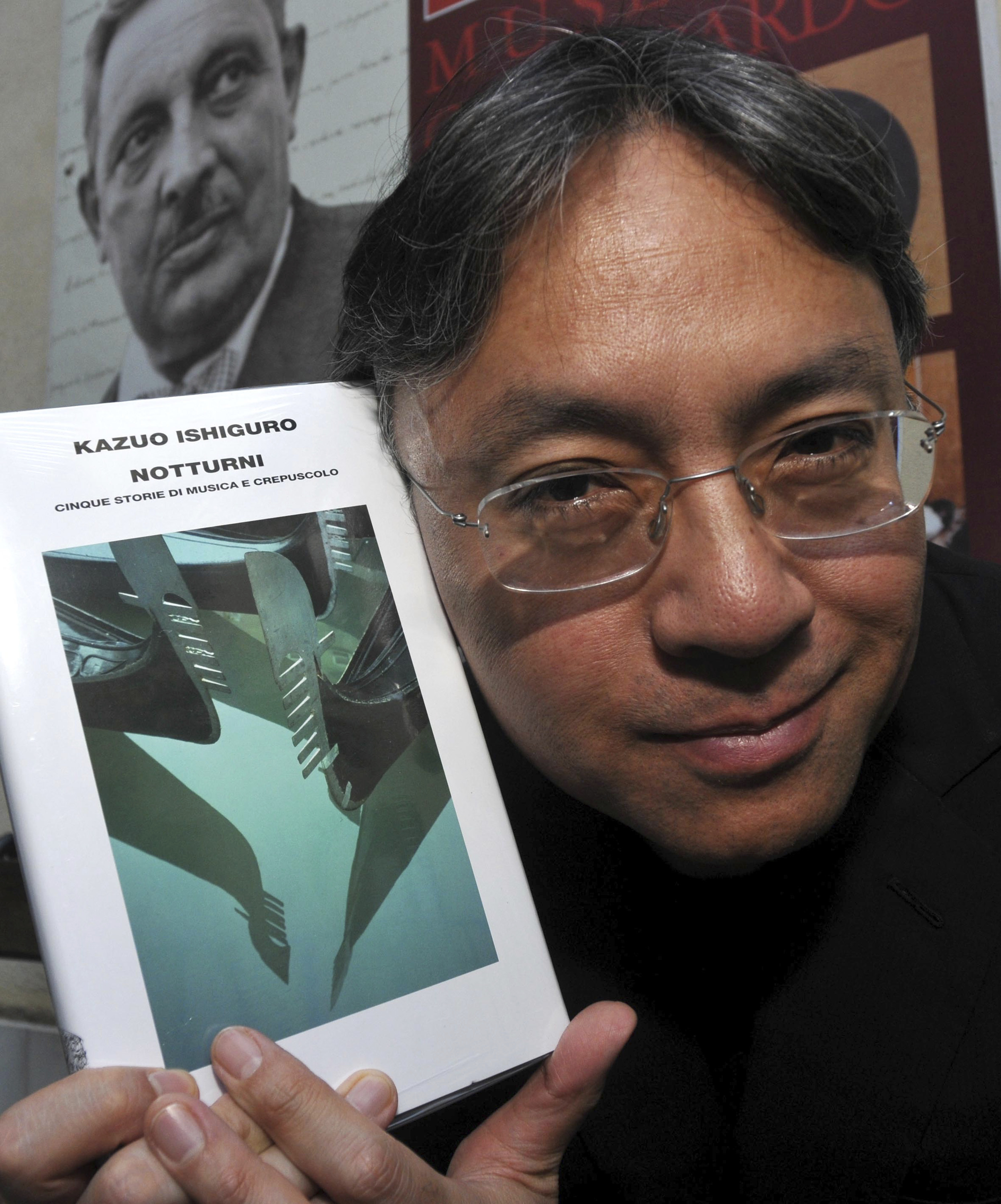 "FILE - In this Saturday, Aug 8, 2009 file photo, author Kazuo Ishiguro shows his book ""Nocturnals"" before receiving the ""Giuseppe Tomasi di Lampedusa"" prize for literature, in Santa Margherita Belice, near Palermo, Sicily, southern Italy.  The Nobel Prize for Literature for 2017 has been awarded to British novelist Kazuo Ishiguro, it was announced on Thursday, Oct. 5, 2017. (AP Photo/Alessandro Fucarini, File)"