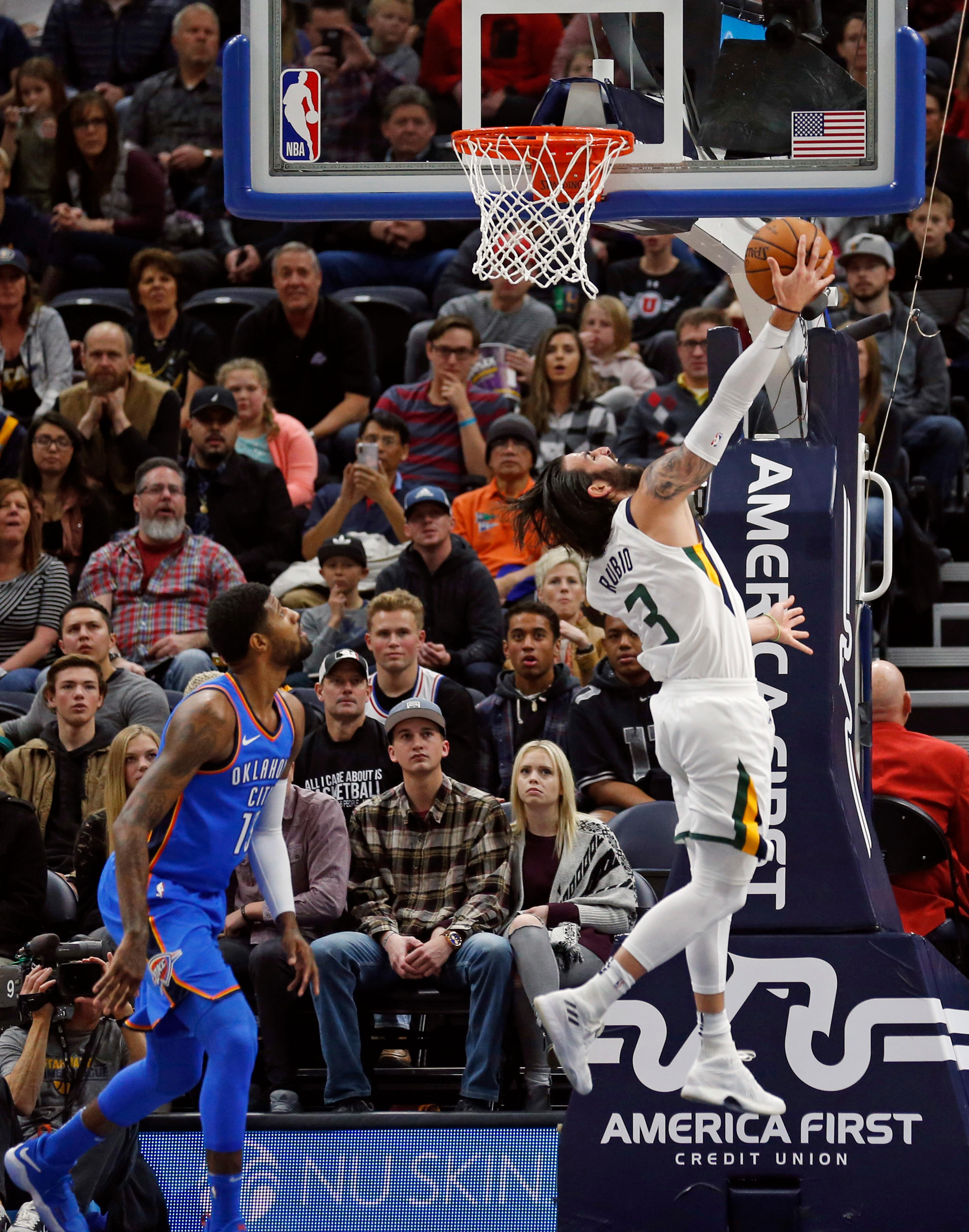 Utah Jazz guard Ricky Rubio (3) lays the ball up as Oklahoma City Thunder forward Paul George, left, looks on in the first half during an NBA basketball game Saturday, Dec. 23, 2017, in Salt Lake City. (AP Photo/Rick Bowmer)