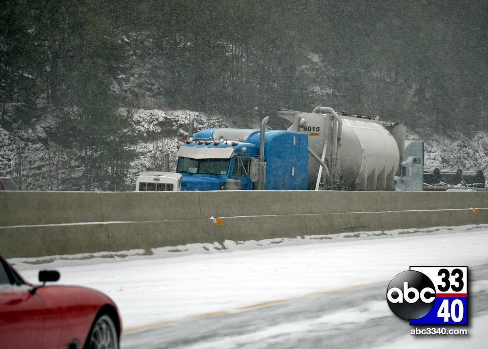 A tractor trailer rests on a guardrail on Interstate 459 East after wrecking during a winter storm in Birmingham, Ala., Tuesday, January 28, 2014.