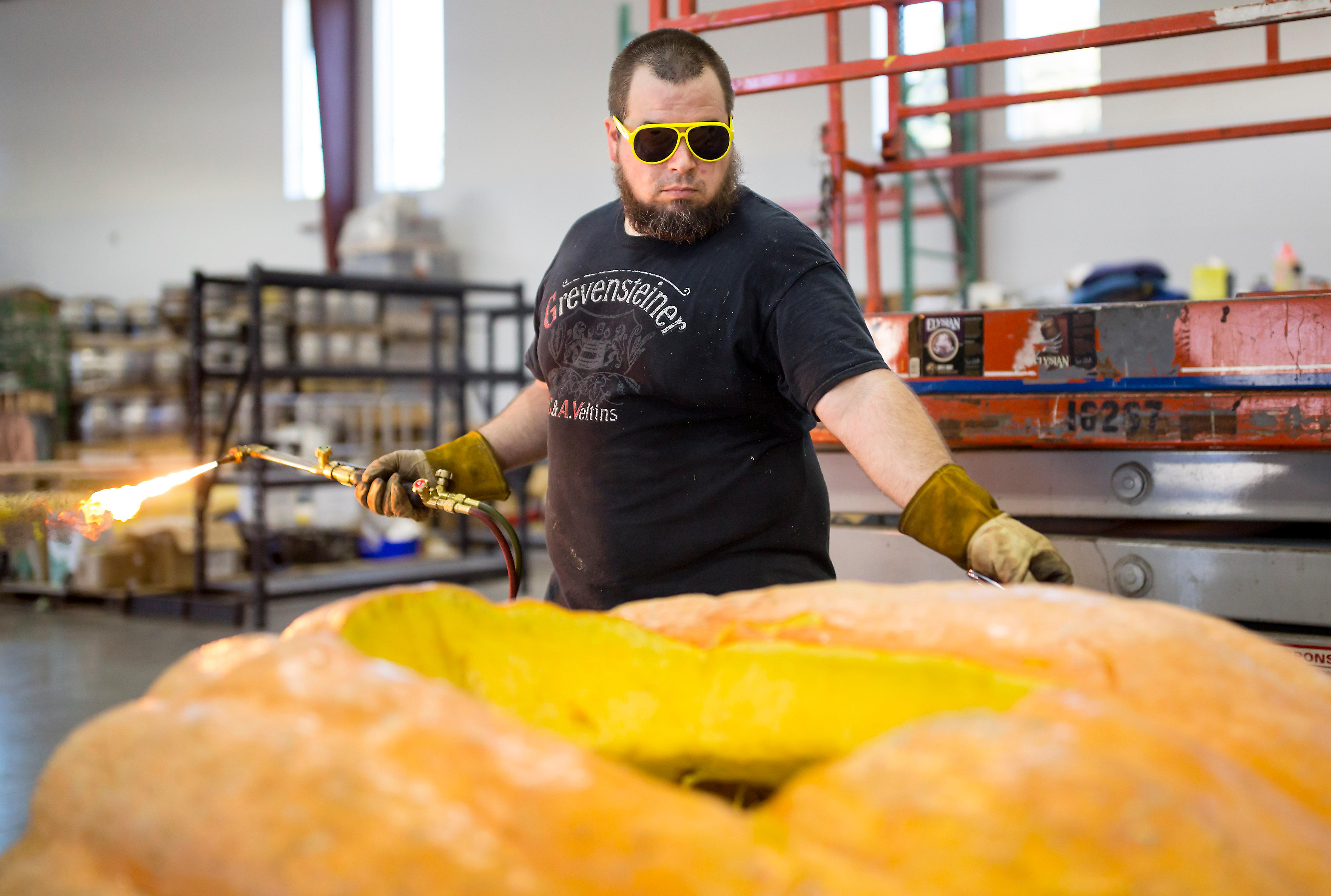 With blowtorch in hand, Elysian cellarmaster Dan-o slowly transforms a massive pumpkin into a usable keg for the Great Pumpkin Beer Festival that will take place this weekend at the Seattle Center. (Sy Bean / Seattle Refined)