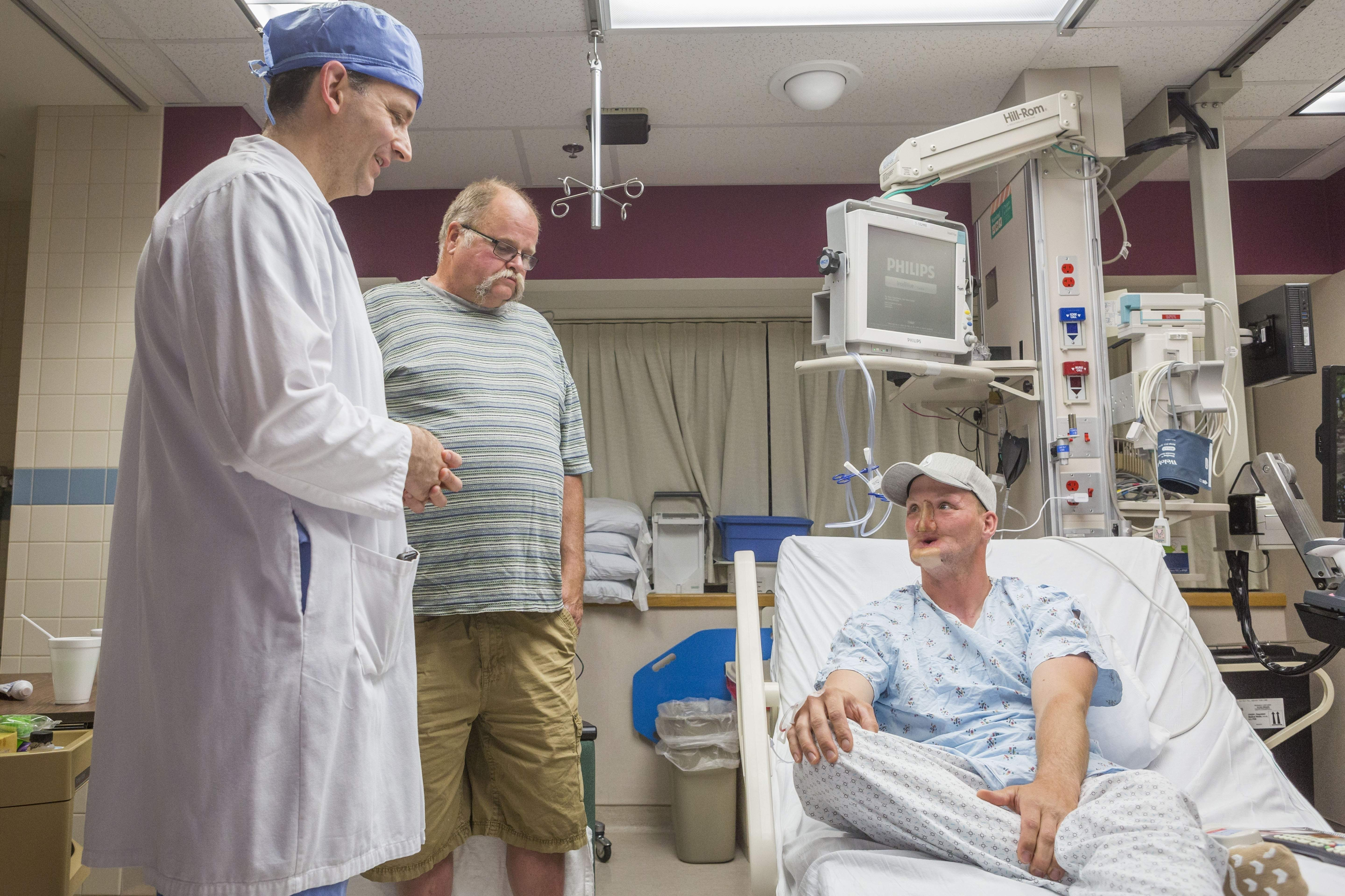 In this June 10, 2016, photo provided by the Mayo Clinic, Andy Sandness, right, talks with his father, Reed Sandness, and Dr. Samir Mardini, left, before Andy's face transplant procedure at the Mayo Clinic in Rochester, Minn. In the process leading up to the surgery, Mardini tried to temper his patient's enthusiasm. 'Think very hard about this,' he said. Only a few dozen transplants have been done around the world, and he wanted Andy to understand the risks and the aftermath: a lifelong regimen of anti-rejection drugs. But Sandness could hardly contain himself. 'How long until I can do this?' he asked. THE ASSOCIATED PRESS