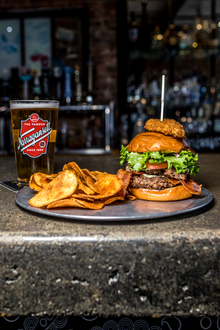 East End Burger: American cheese, bacon, red onion, shredded lettuce, and tomato & garlic aioli served on challah with a fried pickle topper and paired with a Narragansett Lager / Image: Catherine Viox{ }// Published: 3.12.20