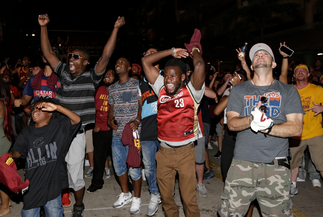 Cleveland Cavalier fans celebrate after the Cavaliers defeated the Golden State Warriors 93-89 in Game 7 of the NBA basketball Finals, Sunday, June 19, 2016, in Cleveland. (AP Photo/Tony Dejak)